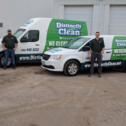 Distinctly Clean employees standing in front of company vehicles